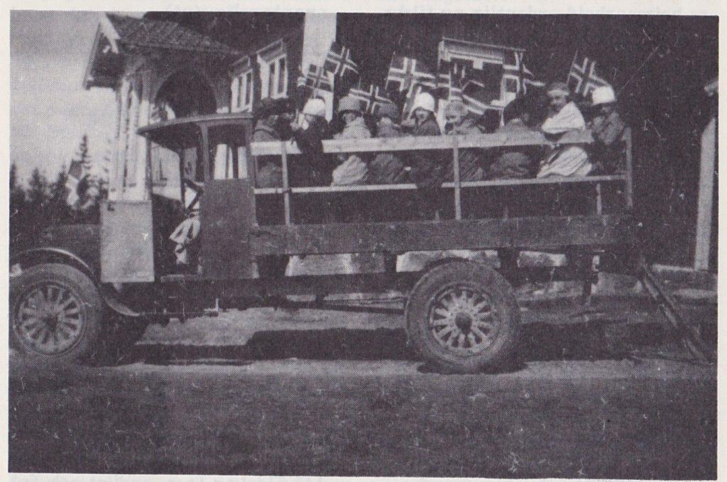 """Skolebarnskyss anno 1930. Elever ved Holseter skole på vei til Eidskog kirke, Matrand, en fin-fin 17. mai-dag. """"Bussen"""" tilhører Martin Melbye."""